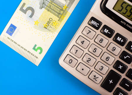 Calculator and euro on a blue background.