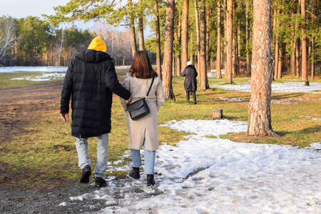 Young boy and young girl are walking in the autumn park. Boy holds the girls arm. Loving couple on a walk. First snow fell. View from the back.