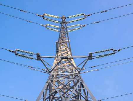 Electric support, illuminated by the bright sun. Metal support for high voltage power lines against the sky. Electrical cables are attached to the pylon on poles through glass insulators.
