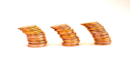 Money coins in a stack are tilted to the side, isolated on a light background. Bundles of coins fall. Economic and financial crisis. Falling exchange rate. Selective focus.