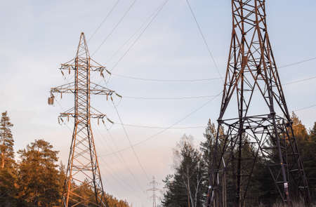 Metal support for high voltage power lines against the sky. Electrical cables are attached to the pylon on poles through glass insulators. Electrical industry. Place for text. Banque d'images