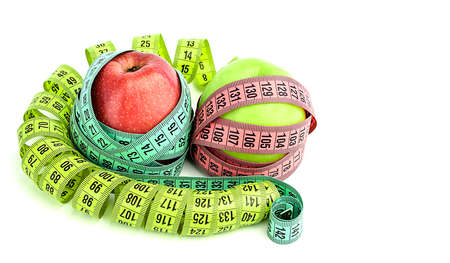 Bright colored measuring tapes, twisted in a spiral around a red and green apple, isolated on a white background. Fitness, diet, weight loss concept. Weight loss.