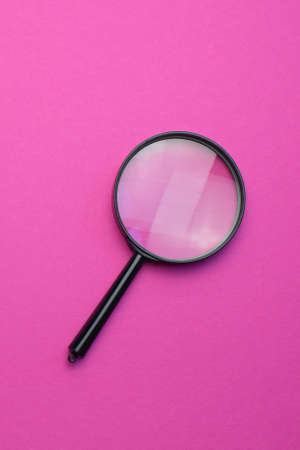 Magnifying glass on a colored background. Top view. Vertical photo. Copy space for text.