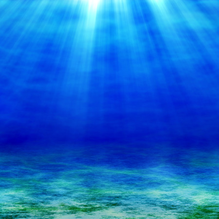 at the bottom of: The sunbeams penetrate the depths of the ocean. Sea and sandy bottom at sunny day.