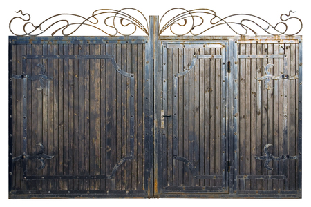 The gate made of wood and metal. Old forged ornament on wooden gate. A high resolution.