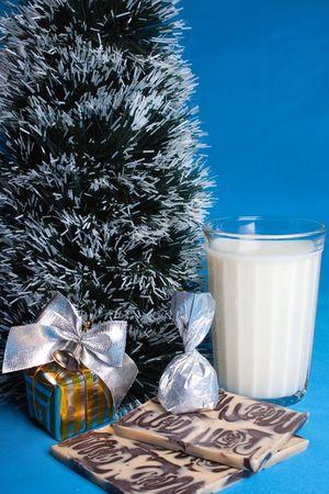 Sweetnesses, milk, croissants and souvenir near the tree of Christmas. photo