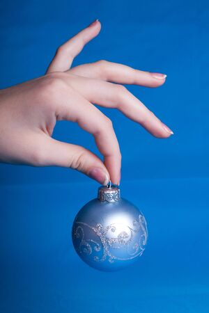Blue Christmas ball in a hand. photo