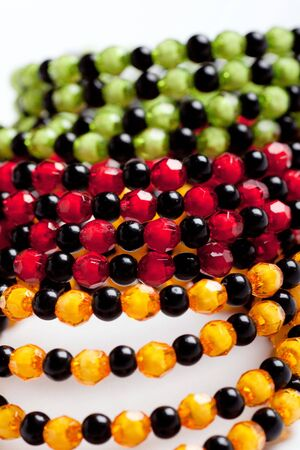Green, yellow, red and black facet beads. photo