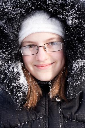 Portrait of the beautiful girl in a fur hood in snow. Stok Fotoğraf