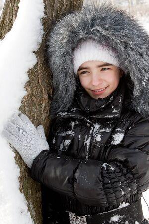 fur hood: beautiful girl near a tree in snow.