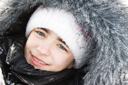 Portrait of the beautiful girl in a fur hood in snow. Stock Photo - 9424045
