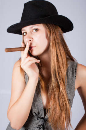 Portrait of the beautiful and stylish girl in a hat with a cigar. photo