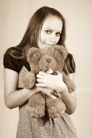Portrait of the beautiful girl with a toy a bear Teddy. photo