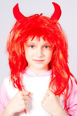 Girl in a red wig with small horns Stock Photo - 9404597