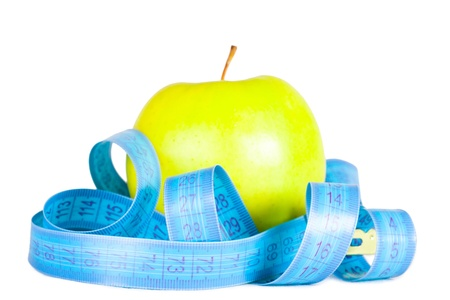 Green apple with a tape of measurements. photo