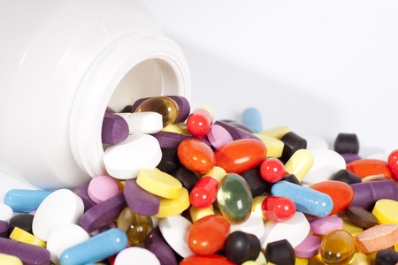 bottle with pills and capsules on white background