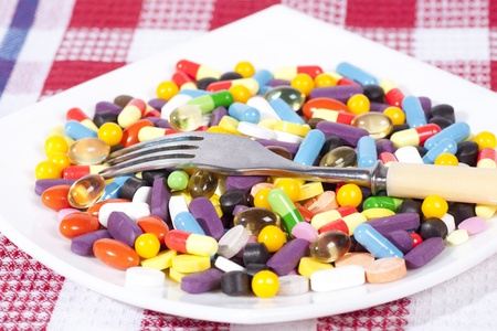 Pills and tablets in a plate with a plug photo