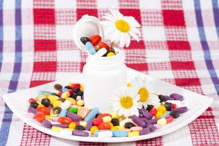 Flowers and full jar of capsules, pills in a plate with medicines photo