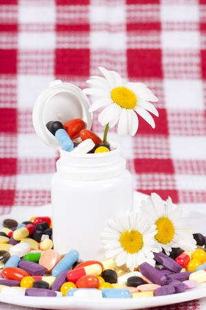 Flowers and full jar of capsules, pills in a plate with medicines Stock Photo - 9876916