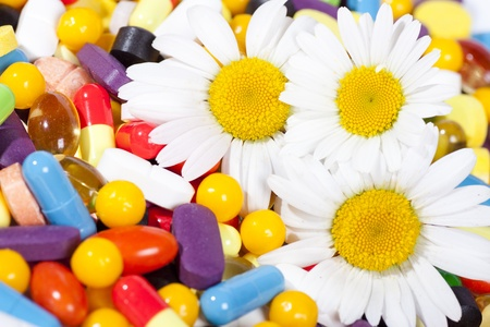 many pills of different color and flowers photo