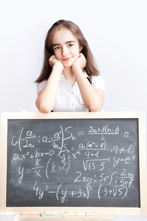 equations: schoolgirl writes the equations and formulas on a school board