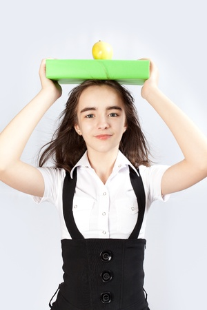 schoolgirl holds the book with an apple on a head photo