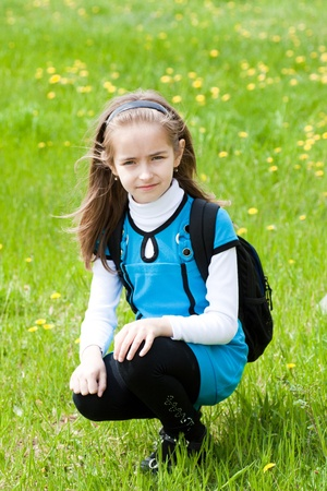 Portrait of the schoolgirl in the field against a green grass photo