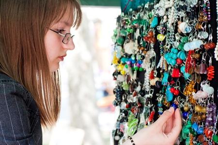young beautiful girl chooses jewelry photo