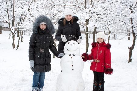 Children build the snowman in park Stok Fotoğraf