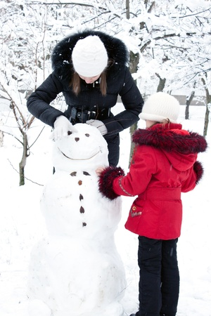 Children build the snowman in park photo