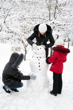 making face: Children build the snowman in park Stock Photo