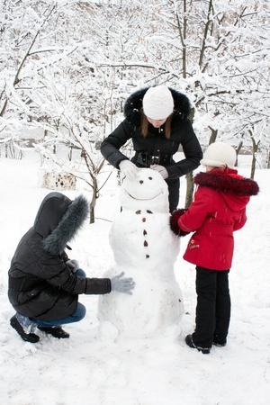 snow girl: Children build the snowman in park Stock Photo