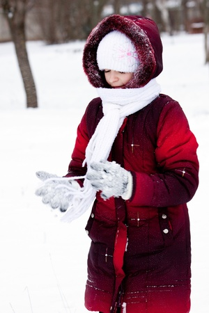 girl in winter clothes plays to snow photo