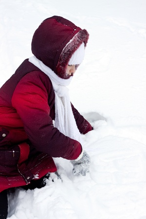 girl draws a hand on snow photo