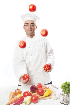 Cook juggles vegetables over white photo