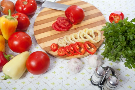 Table with vegetables in kitchen. Knife and cutted tomato photo