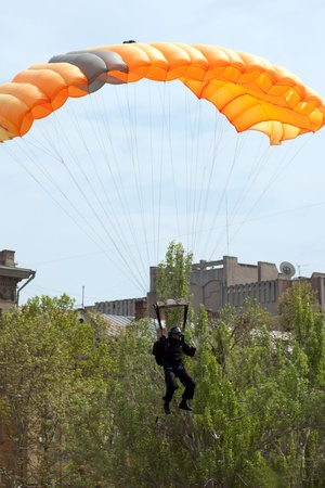 parachutist in the blue sky on a parachute photo