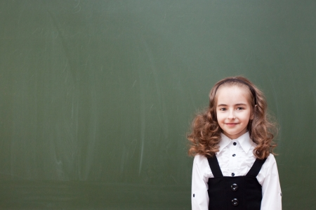 small schoolgirl about a blackboard photo
