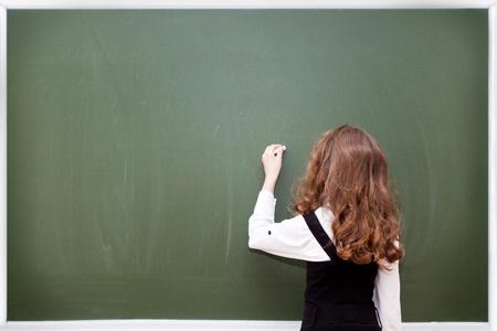 small schoolgirl writes on a blackboard Stok Fotoğraf
