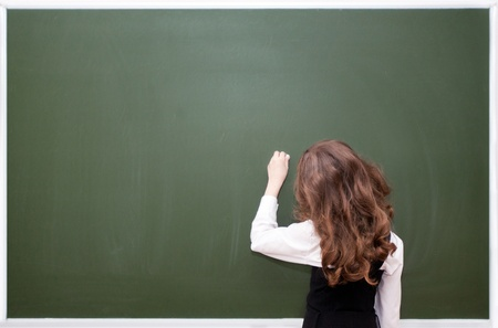 small schoolgirl writes on a blackboard photo