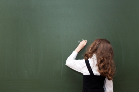 small schoolgirl writes on a blackboard 版權商用圖片