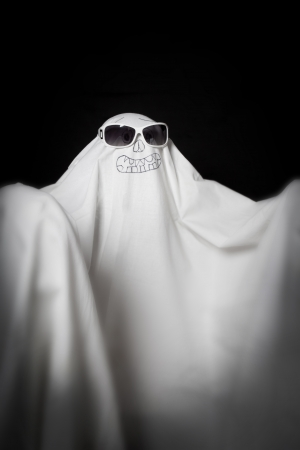 Halloween a ghost in sunglasses in the dark photo