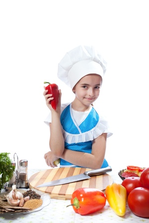 Happy little chef cook with Bell Pepper on white background photo