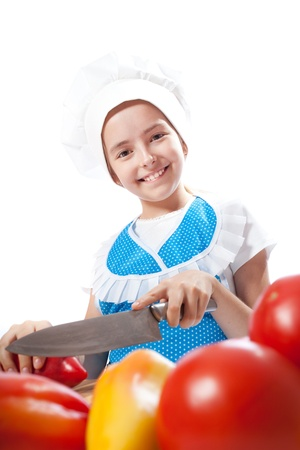 Happy little chef cook cuts Bell Pepper on a white background photo