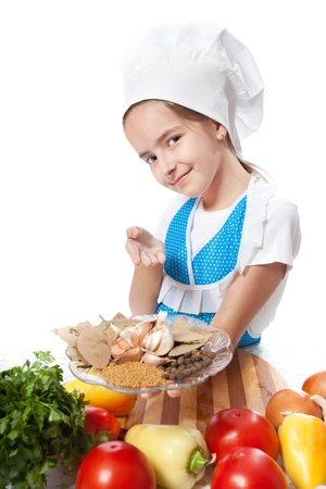 Happy little chef cook offers a plate with spices on a white background photo