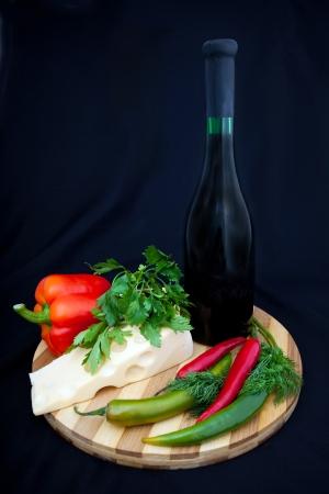 tabla de quesos: botella de vino, queso, pimienta y zelenna de quesos