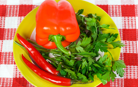 greens parsley, sweet and hot peppers in a bowl photo