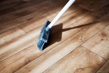 A broom consecrated by the sun rays sweeps dust from a wooden floor, parquet. Shallow depth of field.