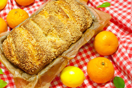 Homemade baking. A hot, aromatic pie with a crispy brown crust. Citrus pie (oranges, tangerines, lemon) in a baking dish. Christmas cake. Red and white checkered fabric background. Rich pastries. Stock fotó