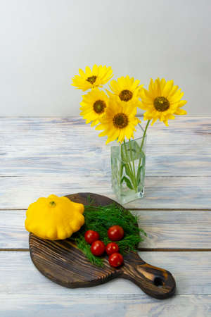 Still life of yellow flowers in glass vase and vegetables on wooden table. Cherry tomatoes, mini patty pan squashes, dill. Healthy food concept.